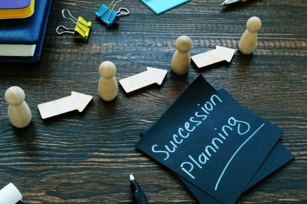 Desk with post it note with 'succession planning' written on it and arrows pointing through figurines