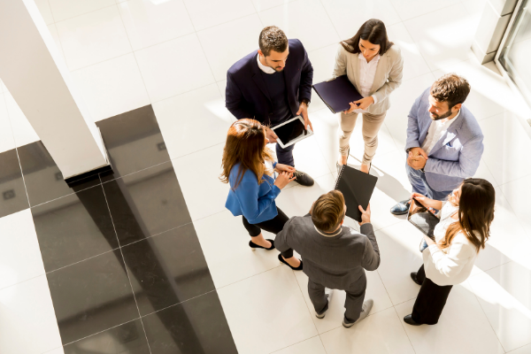 Birds eye picture of business people standing in a circle.