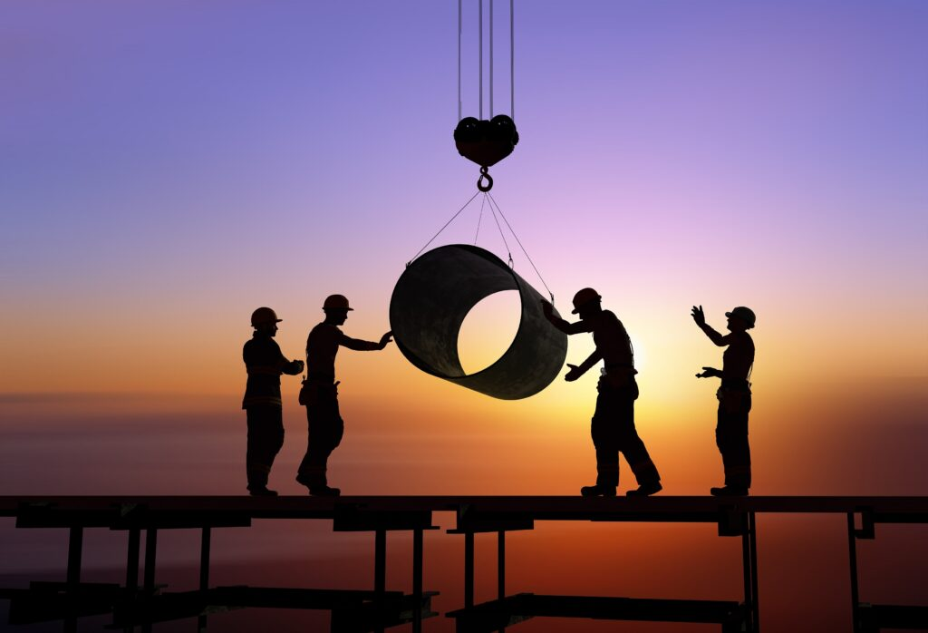 Outline of workers on a construction site with the sun setting in the background.